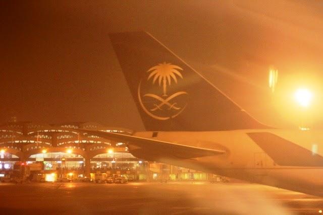 夜のリヤド空港とサウディア航空のロゴ