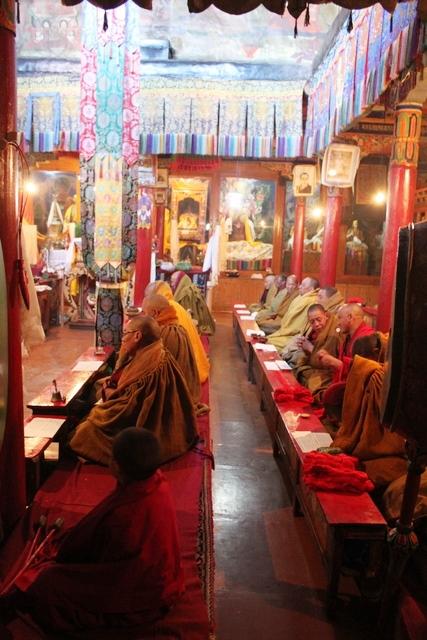 僧院でお経を読み上げる僧侶たち